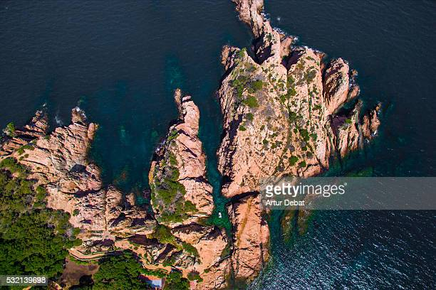 Aerial picture taken with drone of a leisure boat between two crags and green crystal water in the Catalonia Costa Brava shoreline.