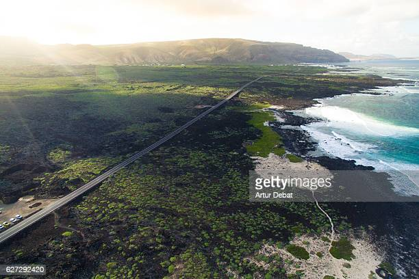Aerial picture taking with drone flying over the beautiful Lanzarote island in the north coast with shoreline and stunning plane, long straight road and nice sunset light on the mountains.