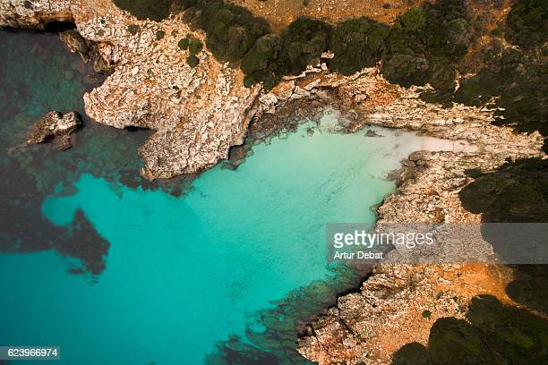 Aerial picture taking with drone flying over the beautiful Menorca island with nice hidden idyllic beach with turquoise water and nobody.