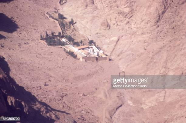 Aerial shot from an airplane flying over a walled citadel or fortress in a valley of the Sinai Desert Israel November 1967