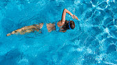 Aerial top view of girl in swimming pool water from above, tropical vacation holiday concept