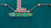 Aerial view Crude oil tanker under cargo operations on typical shore station with clearly visible mechanical loading arms and pipeline infrastructure.