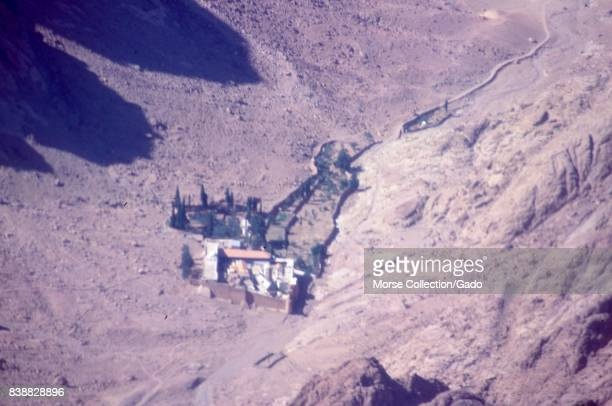 Aerial view from an airplane flying over a walled citadel or fortress in a valley in the Sinai Desert Israel November 1967