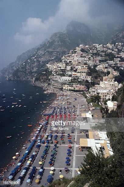 Aerial view looking down on sunbathers and parasols on the beach at Positano Italy 1979 The view looks north along the coastline