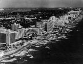 Aerial view looking North which shows the oceanfront luxury resort hotels of Miami Beach Florida 1950s or 1960s Prominant buildings include the...