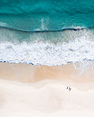 Aerial view of a beach at sunrise, waves and beautiful blue, turquoise water