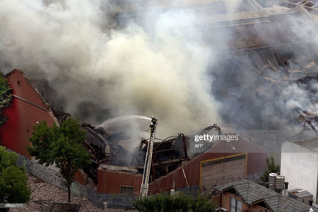 Aerial view of a fire at a warehouse in Barracas, in southern Buenos Aires, on February 5, 2014. At least nine firefighters and rescue workers were killed in Buenos Aires Wednesday when the wall of a warehouse engulfed by flames collapsed on top of them, officials said. Security Secretary Sergio Berni told reporters that several other first responders who were badly injured in the accident were 'fighting for their lives.' Officials said they do not know what caused the blaze in the 19th century era building, which was unoccupied at the time and housed archival bank records.