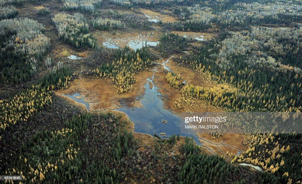 Aerial view of a lake and forests in the vicinity of oil sands extraction facilities near the town of Fort McMurray in Alberta Province Canada on...