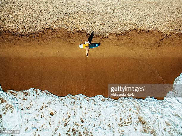 Aerial view of a surfer girl resting on a beach