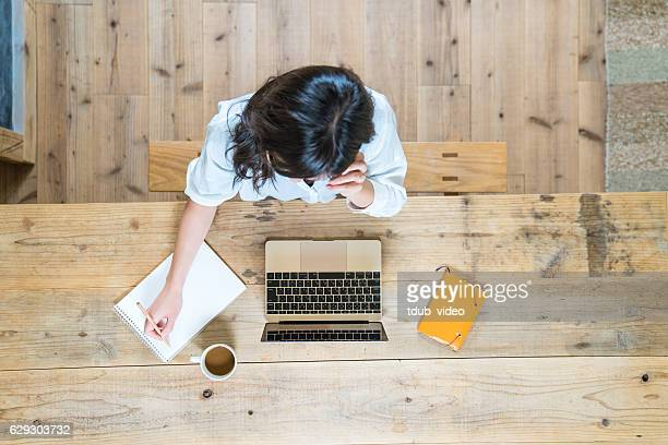 Aerial view of a young woman studying at home