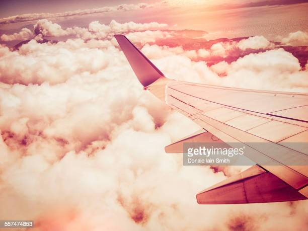 Aerial view of airplane wing flying over clouds in sky