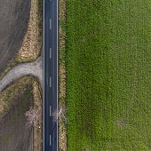 Aerial view of an asphalted country road in Germany with a farmland on the left and a green meadow on the right side. Abstract impression due to vertical angle of view. Made with drone