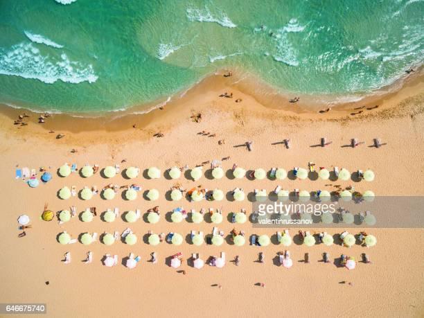 Luftaufnahme von Strand mit Sonnenschirmen
