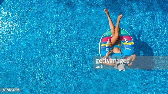 Luftaufnahme von schönen Mädchen im Schwimmbad von oben schwimmen auf aufblasbaren Ring Donut und hat Spaß im Wasser auf Familienurlaub : Stock-Foto