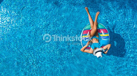 Aerial view of beautiful girl in swimming pool from above, swim on inflatable ring donut and has fun in water on family vacation : Stock Photo