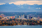 Bellevue, Washington. The snowy Alpine Lakes Wilderness mountain peaks rise behind the urban skyline.