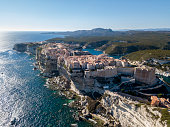 Aerial view of Bonifacio old town built on cliffs of white limestone, cliffs. Harbor. Corsica, France. Strait of Bonifacio separating Corsica from Sardinia