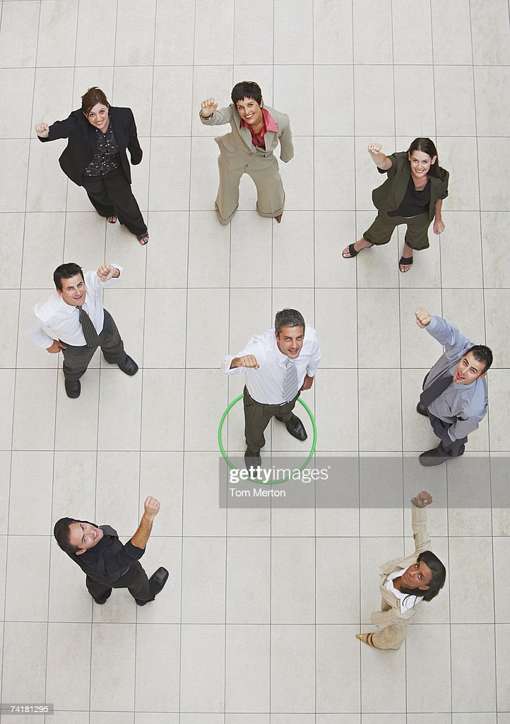 Aerial view of businessman standing in circle with businesspeople cheering : Stock Photo