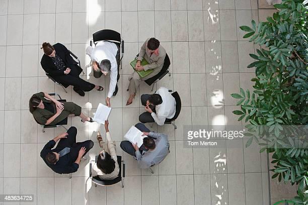 Vue aérienne d'hommes et de femmes d'affaires assis en cercle avec des documents
