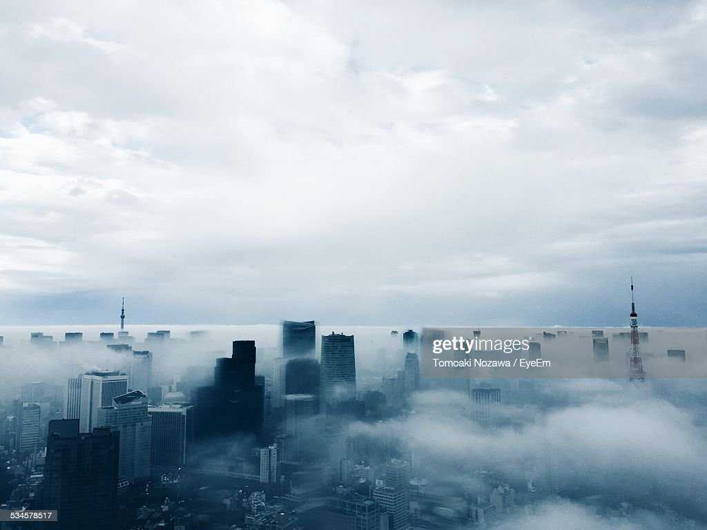 Aerial View Of Cityscape Covered With Fog Against Sky During Dusk