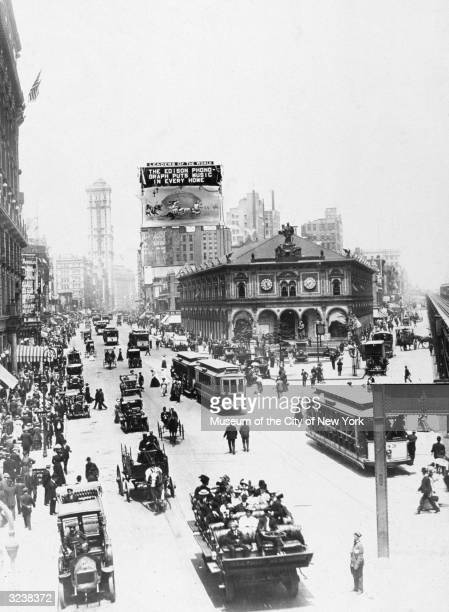 Aerial view of crowds streetcars and carriages traveling down Broadway at Herald Square looking North from 34th Street New York City A billboard...