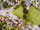 Aerial view of Dutch town, private houses, streets and roundabout, green park with trees