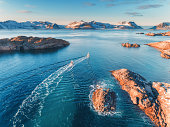 Aerial view of fishing boats, rocks in the blue sea, snowy mountains and colorful sky with clouds at sunset in winter in Lofoten islands, Norway, Landscape with two ship, blue water, waves. Top view