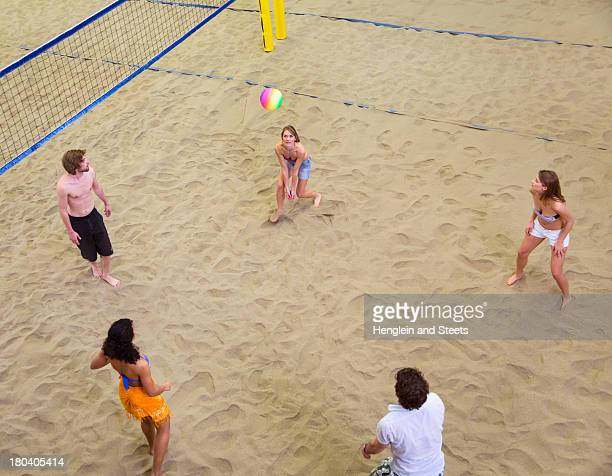 Aerial view of friends playing indoor beach volleyball
