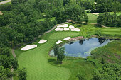 Aerial view of golf course fairway and green with sand traps, pond and trees