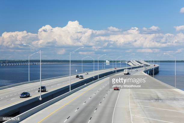 Aerial view of highway bridge across bay under blue sky