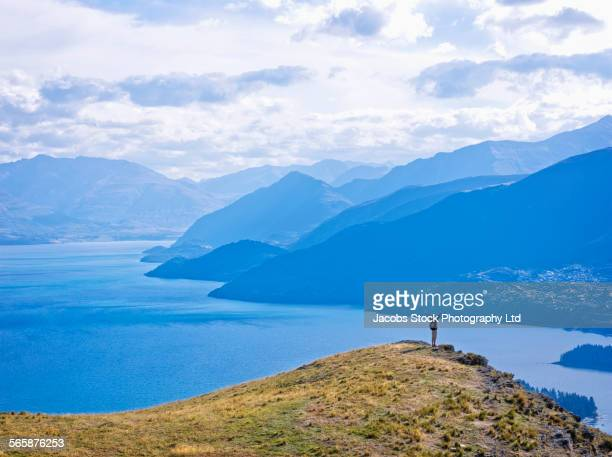 Aerial view of Hispanic hiker cheering on hilltop near lake, Queenstown, South Island, New Zealand