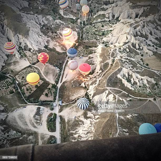 Aerial View Of Hot Air Balloons Flying Over Mountains