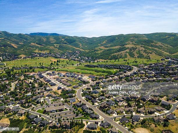 Aerial View Of Houses In City By Mountains Against Cloudy Sky