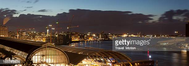 Aerial view of illuminated Amsterdam Central Station at dusk, panorama