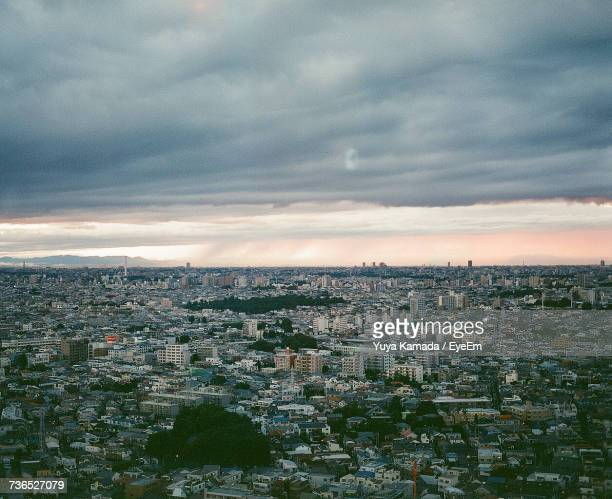 Aerial View Of Illuminated Cityscape Against Dramatic Sky