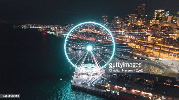 Aerial View Of Illuminated Ferris Wheel By River At Night