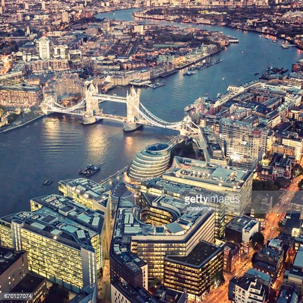 Aerial view of illuminated Tower Bridge and More London at night
