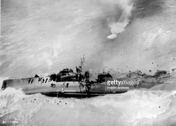 Aerial view of Japanese sailors both in the water and clinging to a sinking ship as it keels over after damage from a American B25 bomber attack 1945