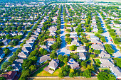 Aerial View of Large Suburb repeated homes and perfect rows of Houses and rooftops looking down on Neighborhood in North Austin near Wells Branch during a great Texas Summer lots of Green at morning r
