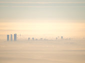 Far aerial cityscape of Madrid city with fog in the morning. Artistic picture