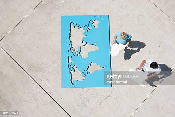 Aerial view of man and woman outdoors with world map puzzle