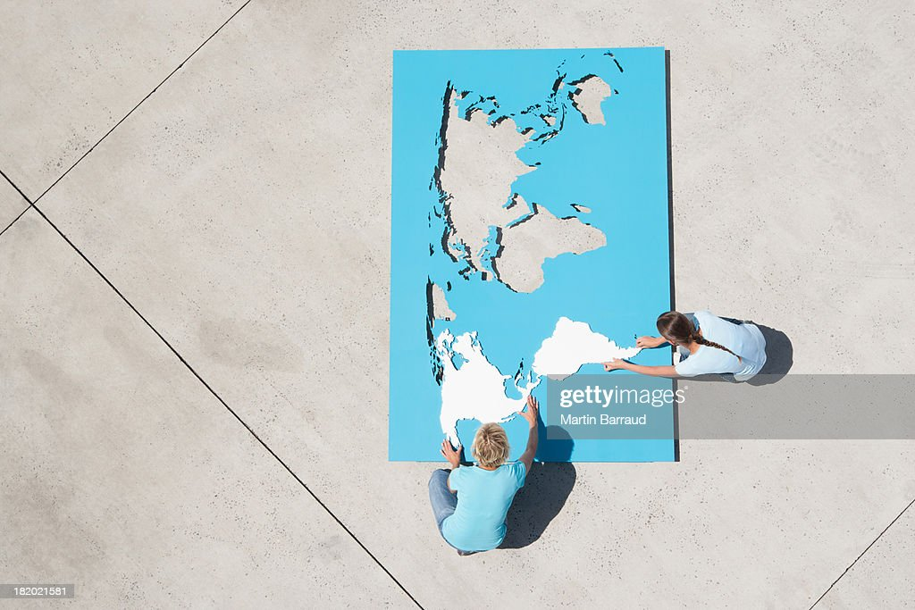 Aerial view of man and woman outdoors with world map puzzle : Stock Photo