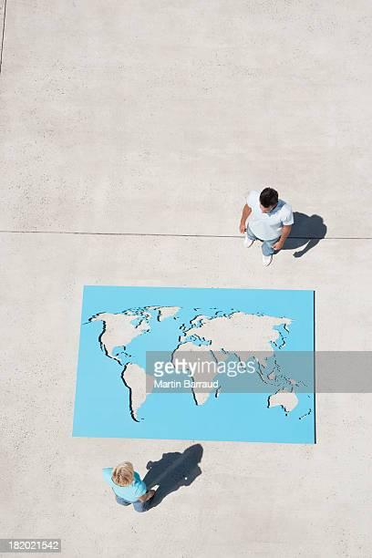 Luftbild von Mann und Frau stehen am world map