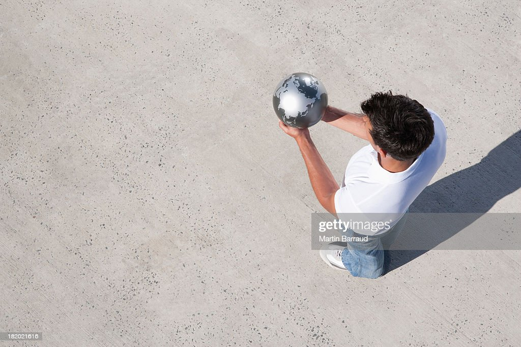 Aerial View of man holding globe outdoors : Stock Photo