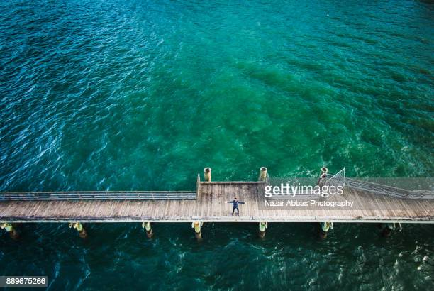 Aerial view of man with outstretched arms on cornwallis wharf, Auckland, New Zealand.