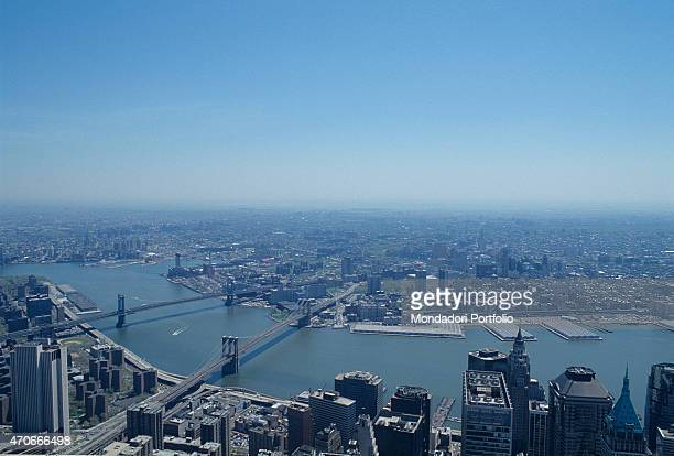 'Aerial view of Manhattan in a sunny day connected by some bridges to the others districts the island is lapped by East River and Hudson rivers New...
