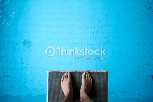 Aerial view of man's feet on diving board on blue : Stock Photo