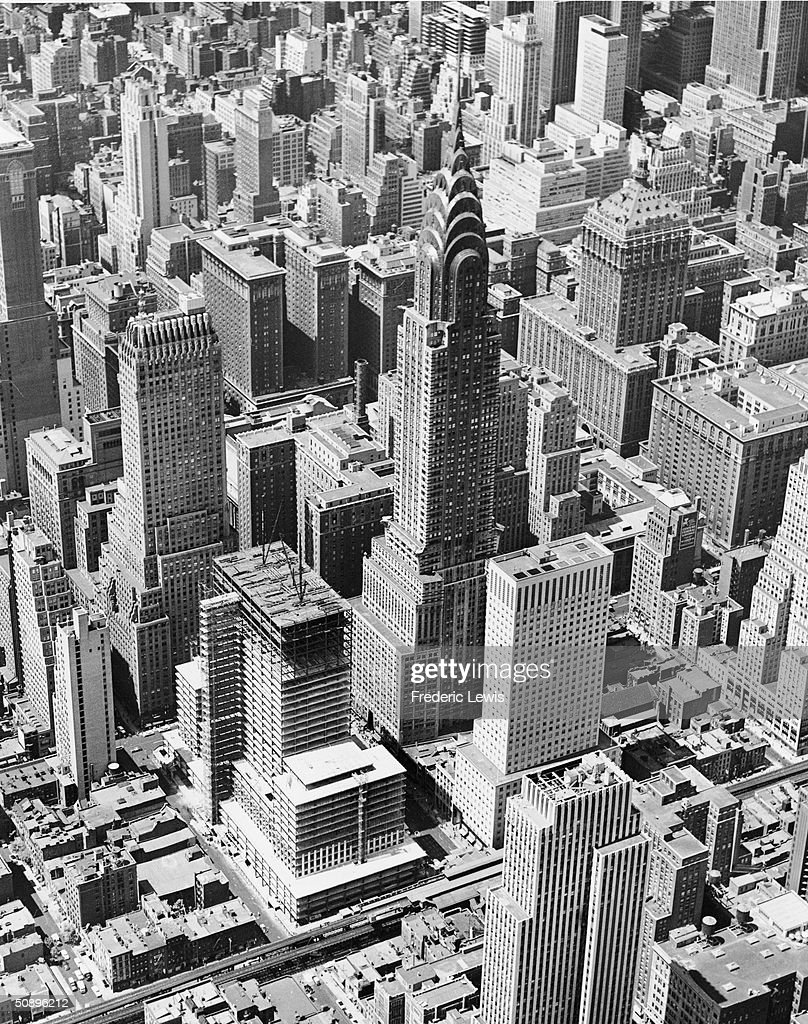 Aerial view of Midtown Manhattan with the Chrysler Building (center), and the Socony-Mobil Bulding (left center, under construction), New York, 1955. The Third Avenue elevated train (#8 line) is visible running diagonally along the bottom.
