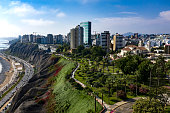Aerial view of Miraflores shoreline including Domodossola park and Larcomar shopping mall. Clear and bright day, travel and destinations concept. Drone aerial shot of Lima's cityscape.