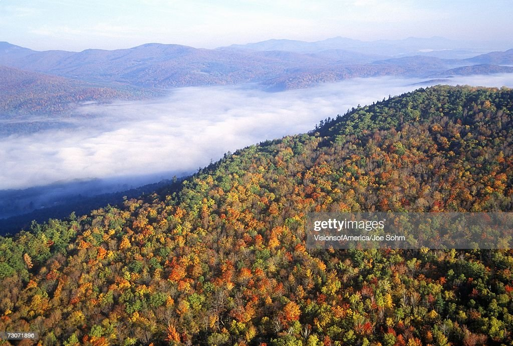 'Aerial view of morning fog over mountains near Stowe, VT in autumn along Scenic Route 100'